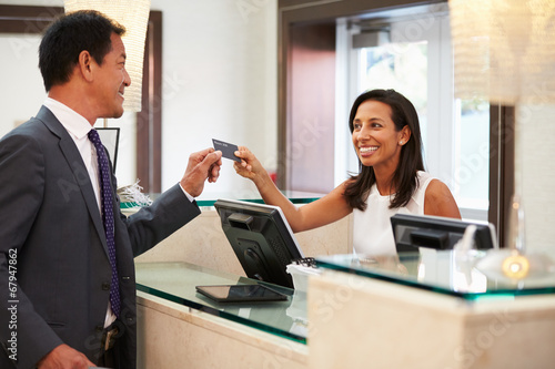 Businessman Checking In At Hotel Reception Front Desk - 67947862