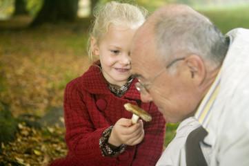 Großvater und Enkelin sucht Pilze im Wald