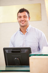 Portrait Of Male Receptionist At Hotel Front Desk