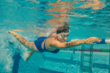 Female participants gushing through water in swimming competitio