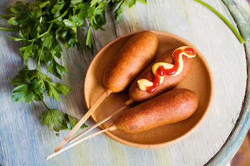 corndog with mustard, ketchup and parsley