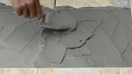 Plasterer spreading concrete on floor