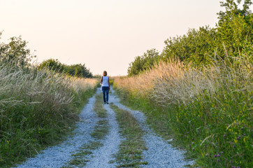 Woman walking at a gravel road at summer