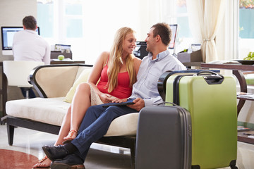 Couple Sitting In Hotel Lobby With Luggage