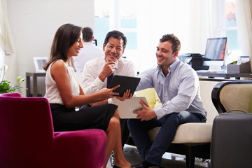 Three Businesspeople Having Meeting In Hotel Lobby
