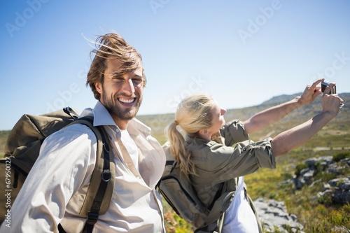 Hiking couple standing on mountain terrain taking a selfie © WavebreakmediaMicro