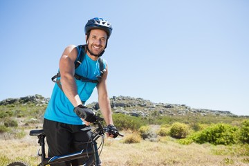 Fit cyclist riding in the countryside smiling at camera