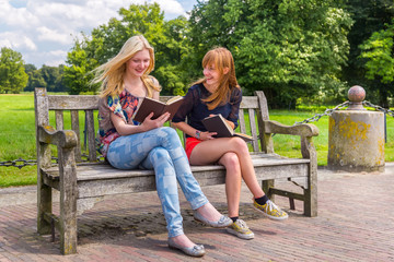 Girls sitting on wooden bench in park reading books