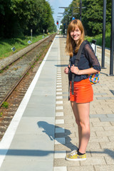 Girl standing at station waiting on train