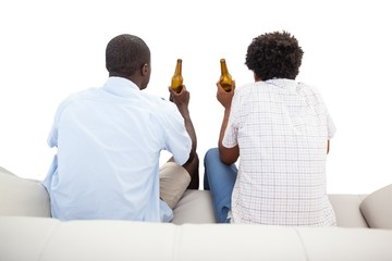 Two sports fans sitting on the couch with beers