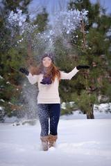 beautiful girl in winter snow throws hands