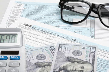 Tax Form 1040 with glasses, calculator and 100 US dollar bills