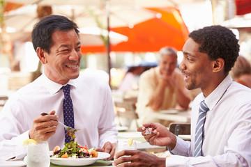 Two Businessmen Having Meeting In Outdoor Restaurant