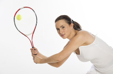 Attractive female tennis player holds raquet with two hands