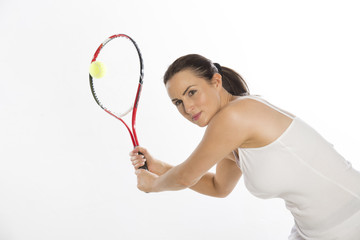 Attractive female tennis player holds the raquet with two hands
