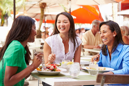 Group Of Female Friends Enjoying Lunch In Outdoor Restaurant