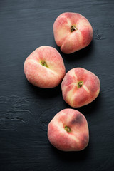 Saturn peaches over black wooden background, above view