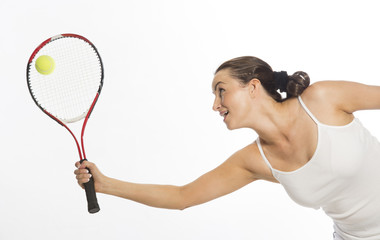Female tennis player stretching to hit the ball