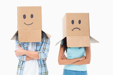 Young couple wearing sad face boxes over head