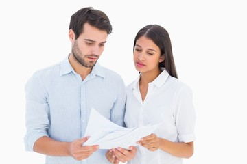 Attractive young couple reading their bills