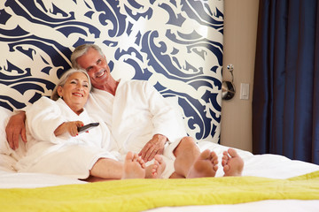 Senior Couple Relaxing In Hotel Room Watching Television