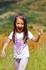 Little girl is playing while running on green-yellow meadow