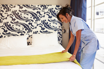 Maid Tidying Hotel Room And Making Bed