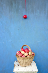 wicker wooden basket with red apples on seat