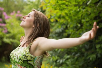 Woman with arms outstretched in field