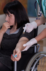 Nurse doing injection to disabled woman