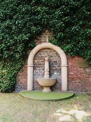 Brunnen  an begrünter  Hauswand