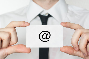 At symbol. Businessman holding business card