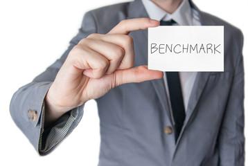 Benchmark. Businessman holding business card