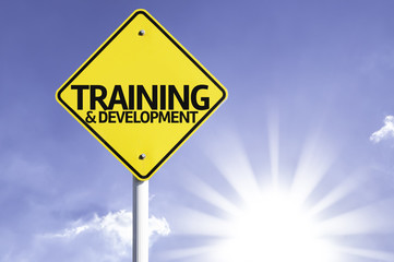 Training & Development road sign with sun background