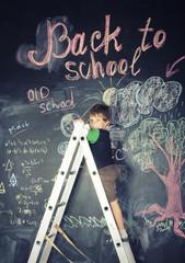 little cute boy at blackboard in classroom