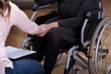 Therapist comforting disabled woman