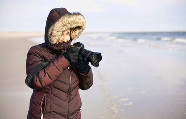 Female photographer on winter beach