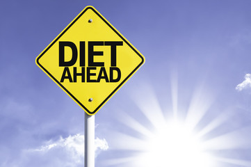 Diet Ahead road sign with sun background