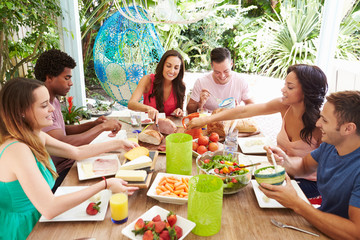 Group Of Friends Enjoying Meal Outdoors At Home
