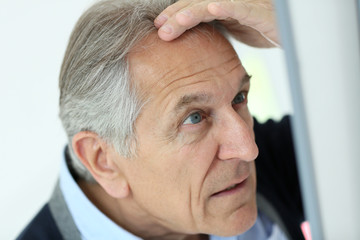 Senior man looking at hair loss in mirror