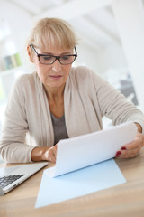 Senior woman filling form online with laptop