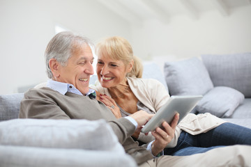 Cheerful senior people websurfing on internet with tablet