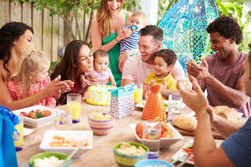 Group Of Families Celebrating Child's Birthday At Home
