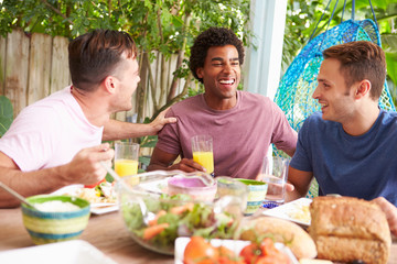 Three Male Friends Enjoying Meal Outdoors At Home