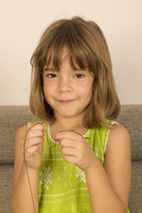 Little girl making a necklace