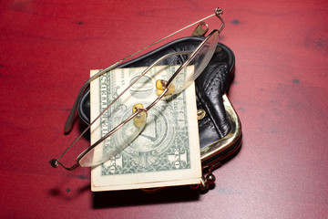 purse, glasses for a correction sight and paper note dollar