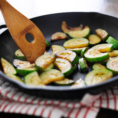 stirring fried zucchini in an iron skillet