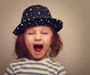 Angry shouting kid girl with open mouth. Vintage portrait