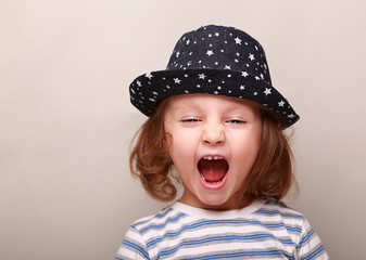 Screaming kid girl in hat with open mouth on empty space