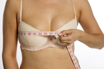 Woman using a tape measure to make bust measurement in inches
